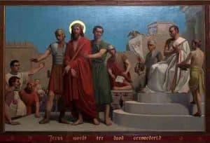 """Op de eerste statie staat behalve Jezus, Pontius Pilatus, de Romeinse prefect afgebeeld op zijn rechterstoel en wast zijn handen in onschuld. De geloofsbelijdenis zegt: """"Die geleden heeft Jezus in de man in de rode mantel en Pontius Pilatus zit boven aan de trap. Op het tafereel zijn Romeinse soldaten en omstanders te zien."""