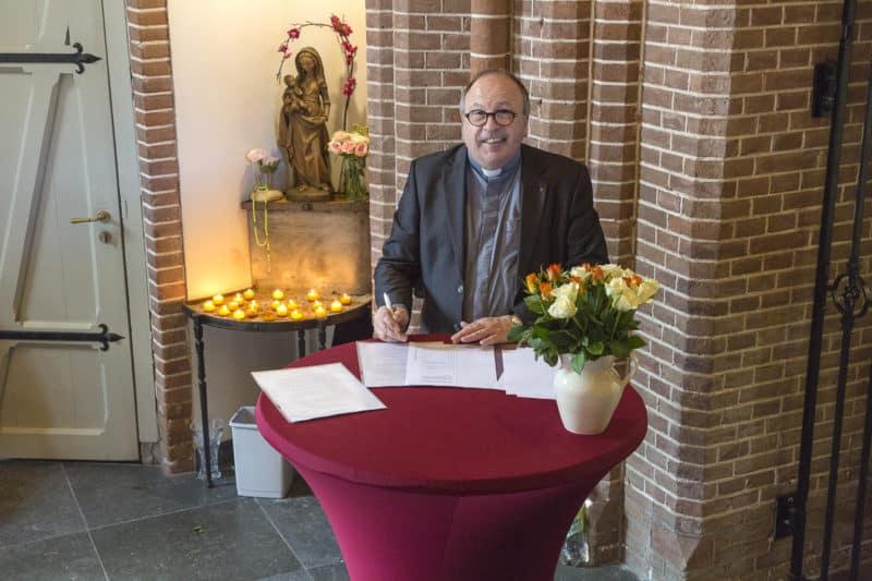 Deken en pastoor E. Jongerden tekent contract met aannemingsbedrijf Nico de Bont